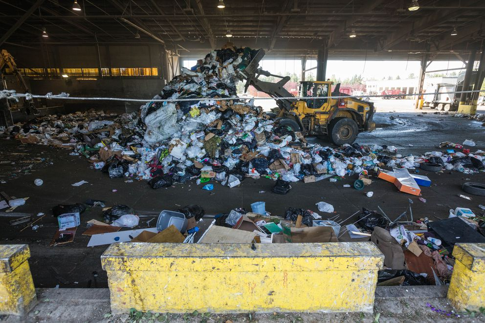 A loader moves trash around the tipping floor at the Central Transfer Station on Friday. (Loren Holmes / ADN)