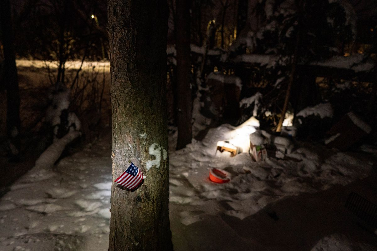 A U.S. flag and an abandoned homeless camp are illuminated by volunteer headlamps during the yearly Point in Time Count on Tuesday night, Jan. 28, 2020 along the Chester Creek greenbelt. The count, required by the U.S. Department of Housing and Urban Development, aims to assist in measuring the extent of homelessness in Anchorage. (Loren Holmes / ADN)