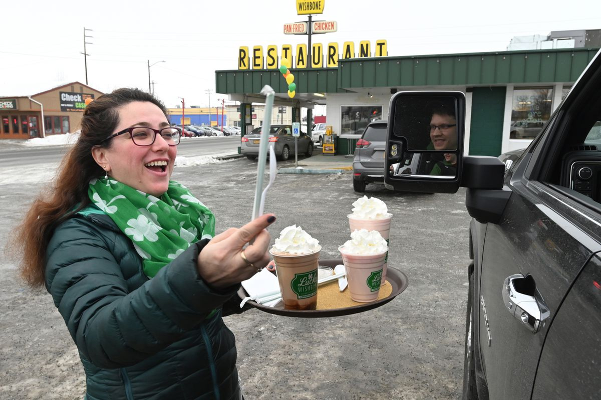 Lucky Wishbone co-owner Carolina Stacey delivers milkshakes to customers in the parking lot on Tuesday, March 17, 2020. On Monday, Anchorage Mayor Ethan Berkowitz issued an order prohibiting dine-in service for food and drinks through March 31. (Bill Roth / ADN)