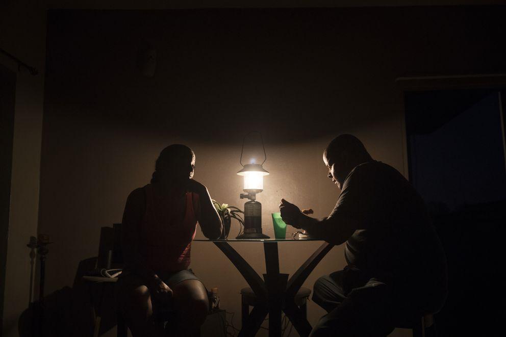 Ana Luz Pérez watches her boyfriend, Carlos Rivera, eat dinner by lantern  light in