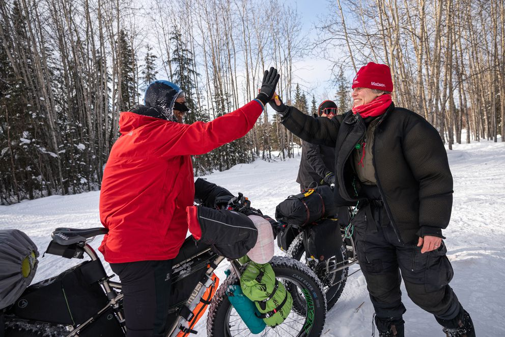 Iditarod musher Aliy Zirkle gives high-fives to Iditarod Trail Invitational bikers George Adams and Graham Muir in Ophir on Wednesday, March 11, 2020. The ITI is a roughly 1,000-mile human-powered race from Willow to Nome that follows the Iditarod trail. (Loren Holmes / ADN)
