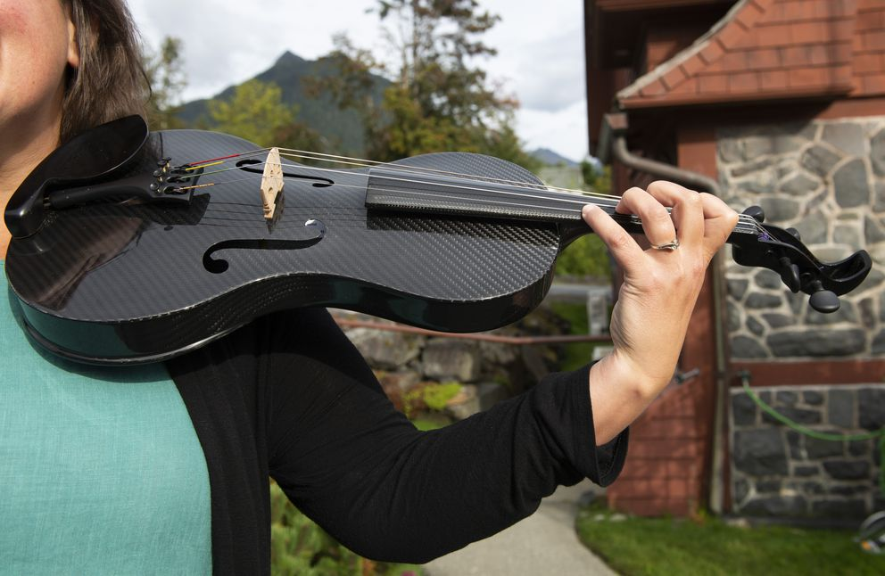 Sitka Summer Music Festival executive director Kayla Boettcher holds one of the festival's carbon fiber instruments at St. Peter's-by-the-Sea Episcopal Church on Thursday, September 5, 2019, in Sitka. (Photo by James Poulson)