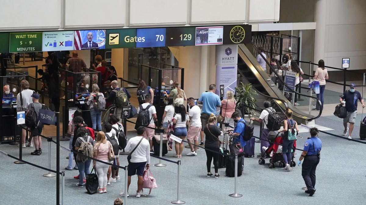 Travelers line up to go through a TSA checkpoint at Orlando International Airport before the Memorial Day weekend Friday, May 28, 2021, in Orlando, Fla. (AP Photo/John Raoux)