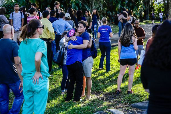 Students and parents embrace after a mass shooting at the Marjory Stoneman Douglas High School in Parkland, Fla., Feb. 14, 2018. At least 17 people were killed Wednesday at this school about an hour northwest of Miami, law enforcement officials said. A suspect, a former student, is in custody. (Saul Martinez/The New York Times)
