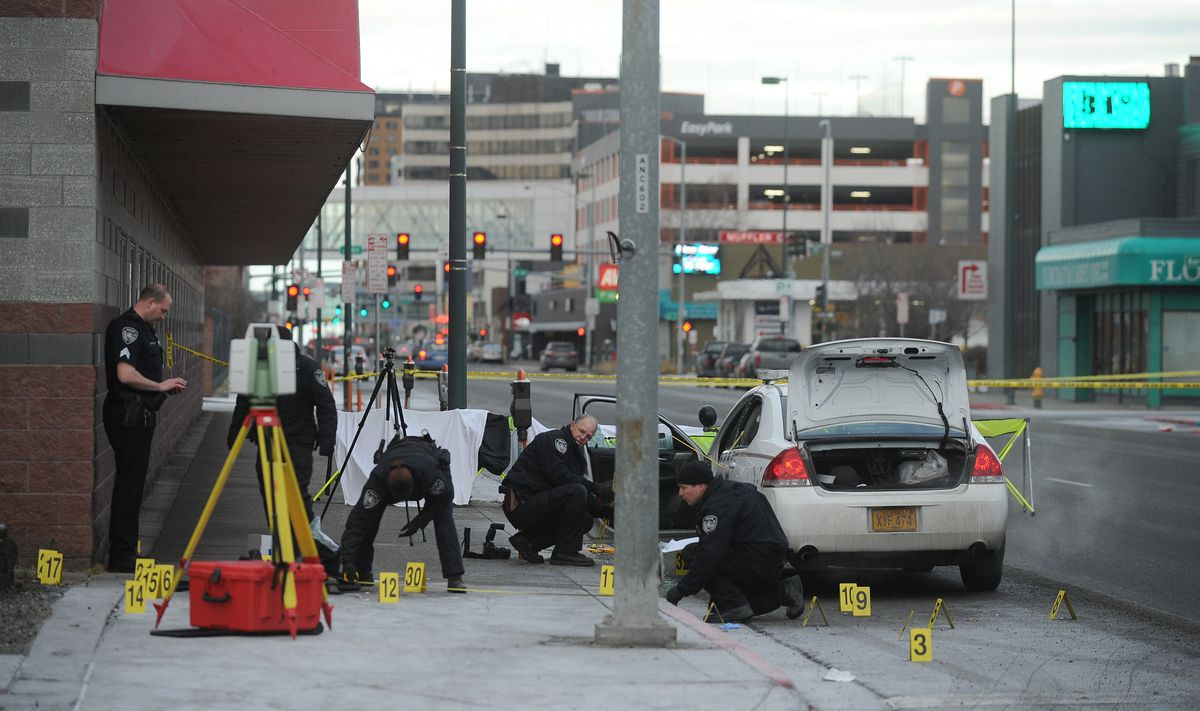 Anchorage police officers investigate the scene of an officer-involved shooting at Fifth Avenue and Cordova Street in Anchorage on November 12, 2016. An APD officer was wounded and the suspect was killed in the early morning shooting. (Bob Hallinen / Alaska Dispatch News)