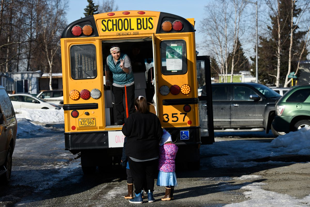 Rosa Edwards served a family at the Dimond Estates mobile home park on March 31, 2020, when the Anchorage School District buses delivered sack lunches and breakfasts to students while schools were closed due to COVID-19. (Marc Lester / ADN)
