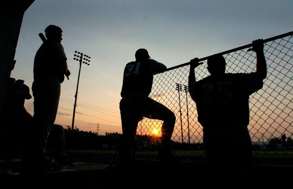 The setting sun peeks through the dugout chain link fence during the 100th annual Midnight Sun Game in Fairbanks. (Jim Lavrakas / ADN archive)