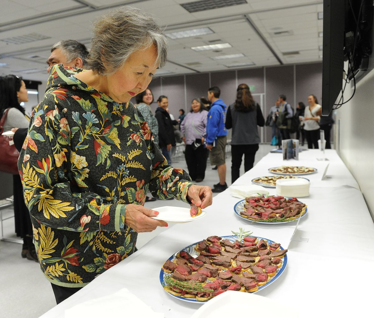 Pearl Johnson, with the Midnight Sun Reindeer Ranch, samples some of their reindeer snacks at Perspectives in Circumpolar Reindeer Production at the Arctic Council event at the University of Alaska Fairbanks on Wednesday. (Bob Hallinen / Alaska Dispatch News)