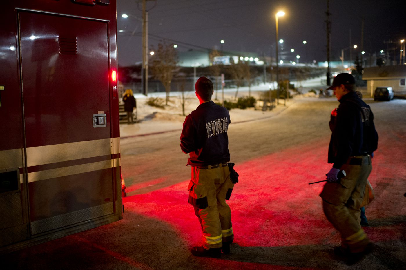 Anchorage firefighters escort a woman from Brother Francis Shelter to an ambulance on Dec. 15. The woman said she was unsure if she overdosed on medication. (Marc Lester / ADN)