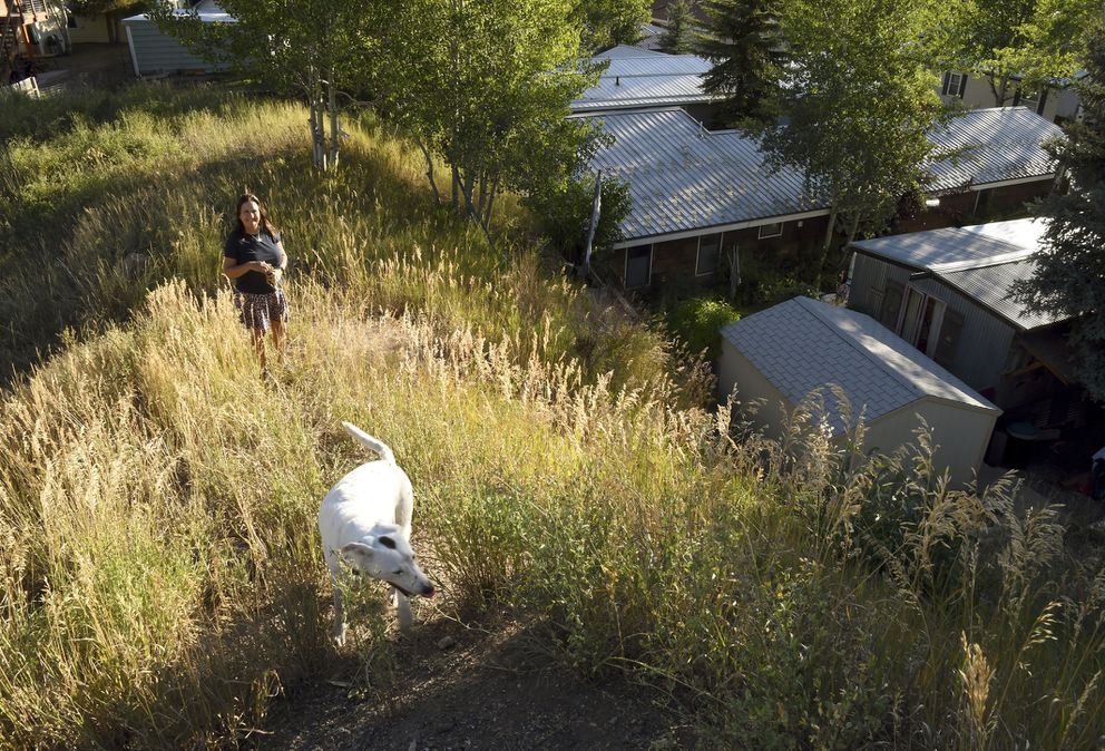 Pitkin County Commissioner Patti Kay-Clapper walks with her dog near her home at the Smuggler Trailer Court outside Aspen, Colo., on Tuesday, Aug. 27, 2019. Clapper says that in the early 1980s, the county allowed Smuggler residents to own their homes and their lots in an effort to keep the community affordable. She now is trying to preserve the county's remaining mobile home parks as affordable housing. (AP Photo/Thomas Peipert)
