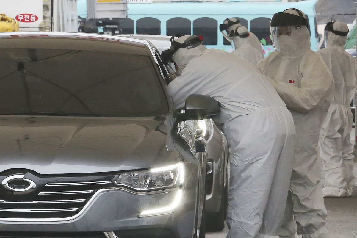 Medical staff wearing protective suits take samples from a driver with symptoms of the coronavirus at a