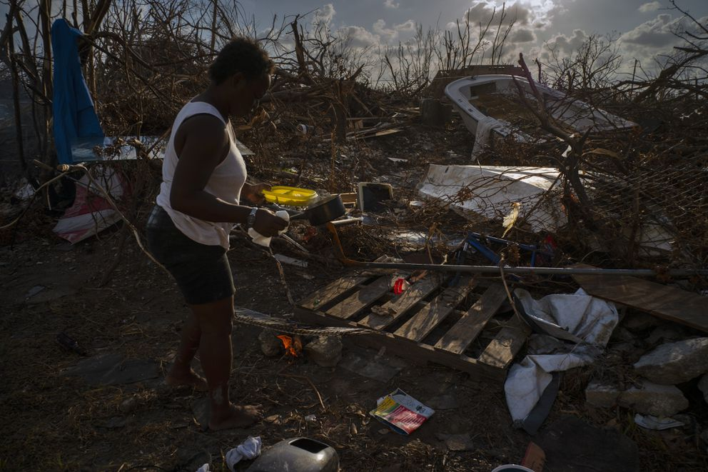 Tereha Davis, 45, holds a plate of rice as she walks among the remains of her shattered belongings, in the aftermath of Hurricane Dorian, in McLean's Town, Grand Bahama, Bahamas, Wednesday Sept. 11, 2019. She and others said they had not seen any government officials and have only received food and water from some nonprofit organizations. (AP Photo/Ramon Espinosa)