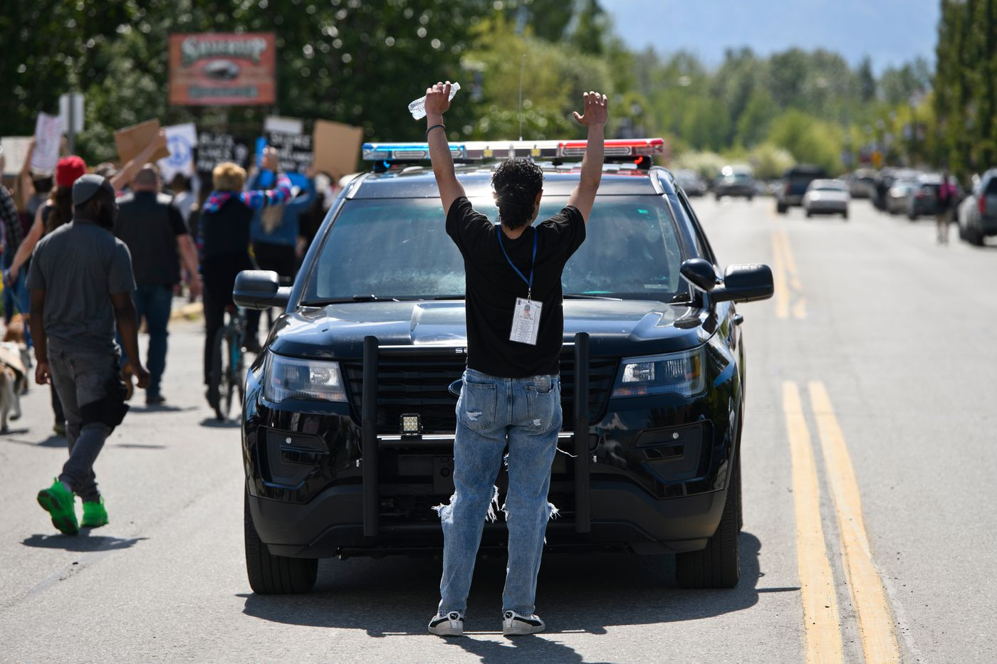 A protester momentarily pauses a Palmer Police vehicle as the march is in progress. A large crowd gathered and marched through Palmer to protest racism and police brutality on Saturday, June 6, 2020. (Marc Lester / ADN)