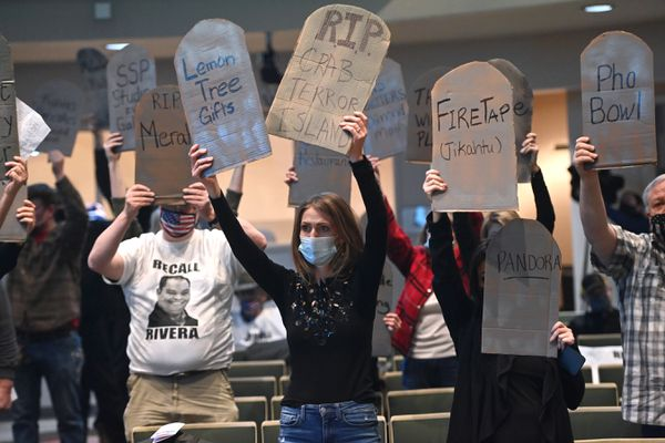 The audience attending the Anchorage Assembly meeting on Tuesday, Jan. 12, 2021, held up cardboard tombstones as Julie Brophy read the names of