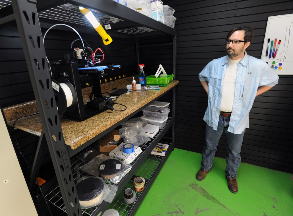 Nick Braman of Alaska Herbal Analysis Labs pauses to watch a 3D printer make a piece of a small plastic lab rack in Wasilla. He keeps the printer busy creating small items while working with suppliers to get the lab geared up after Mat-Su voters rejected a ban on pot businesses this past week. (Erik Hill / Alaska Dispatch News)