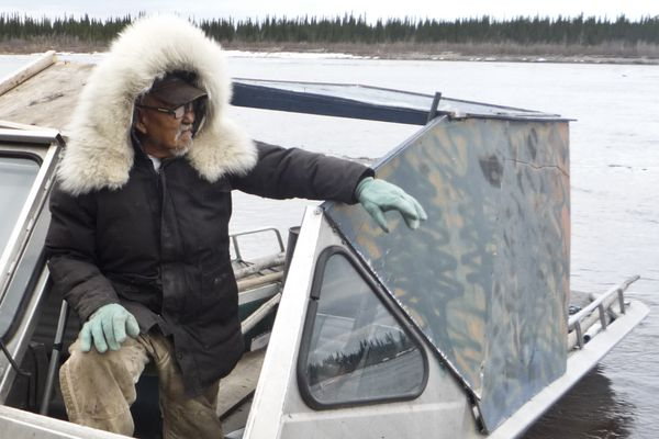 Clarence Wood stands with his boat on the Kobuk River in 2014. (Photo by Stacey Glaser)