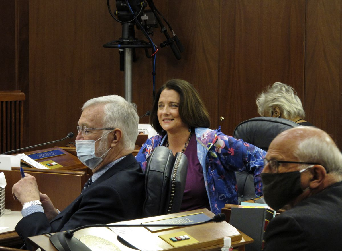 """In this May 18, 2020 photo, Alaska state Sen. Lora Reinbold, center, is shown on the Senate floor in Juneau. Health screenings were required of legislative staff and media at the Alaska Capitol, though lawmakers could skip it. Protocols said masks were required. But Reinbold didn't wear one. """"It didn't make sense to me,"""" Reinbold said."""