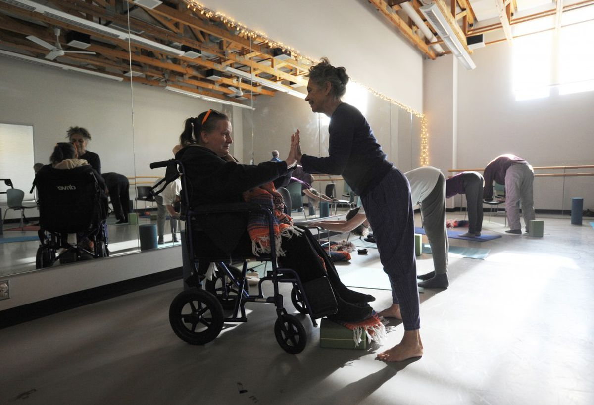 Sherri Hadley, left, works with instructor Rocky Plotnik during a yoga class for people with Parkinson's disease and other movement disorders on Tuesday afternoon, Sept. 27, at Alaska Dance Theatre. (Erik Hill / Alaska Dispatch News)