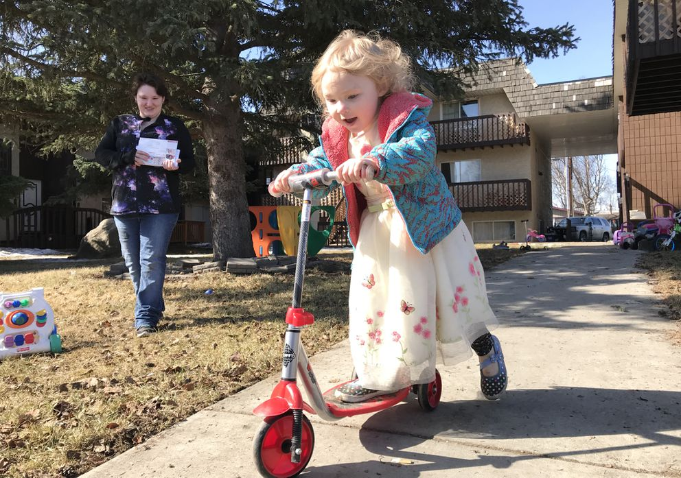 Desiree Britt watches her 4-year-old daughter Vivianne Britt-Andre play on a scooter outside their Mountain View apartment on Sunday. Britt says gunshots have become a regular weekend occurrence in her neighborhood. (Bill Roth / ADN)