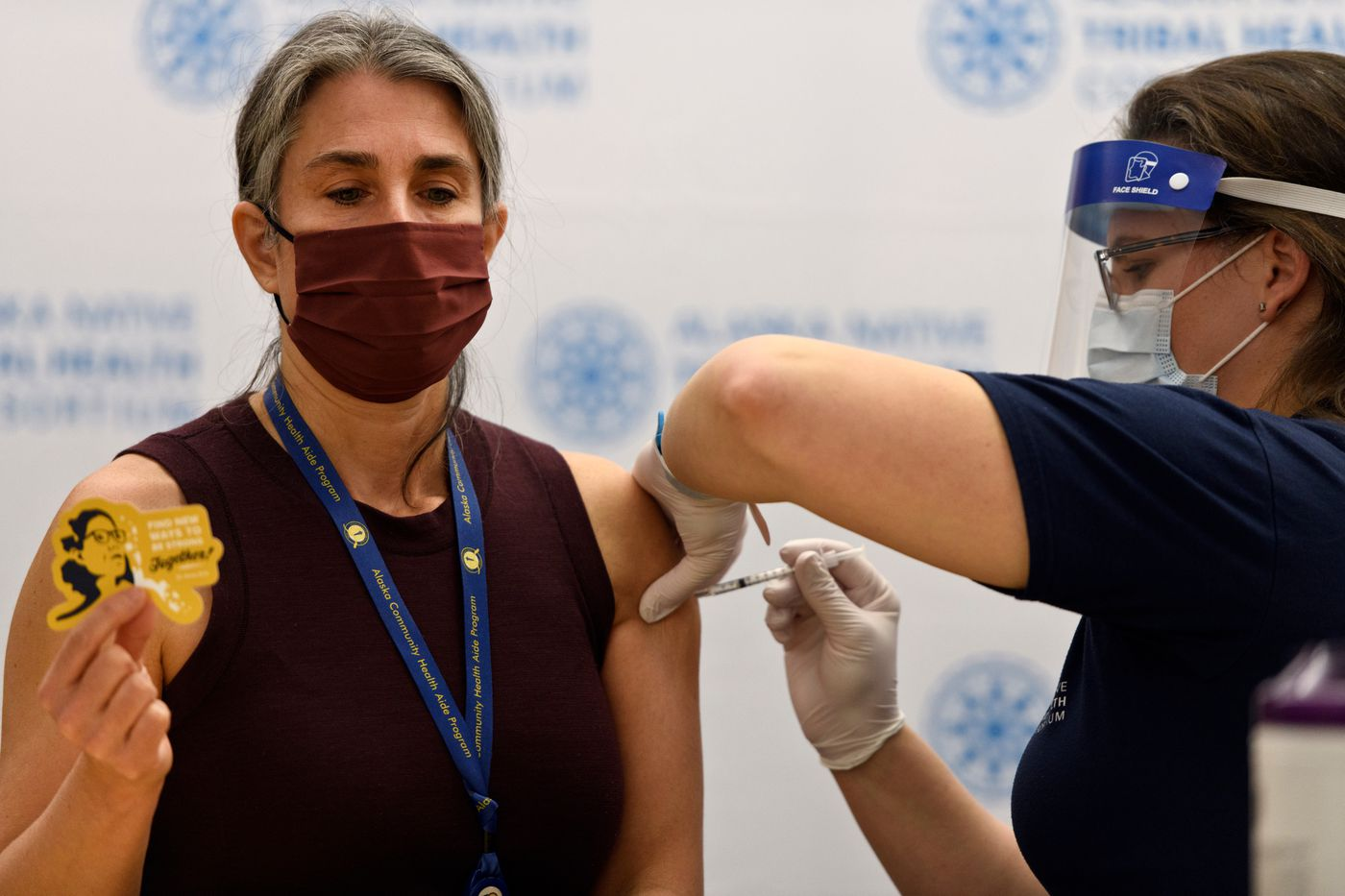 """Dr. Michelle Hensel, a medical director for the Community Health Aide Program, receives her vaccine shot while holding up a sticker with Alaska chief medical officer Anne Zink's image on it. The sticker says """"Find new ways to be strong together."""" Health care workers began receiving vaccination for COVID-19 at Alaska Native Medical Center in Anchorage on December 15, 2020. (Marc Lester / ADN)"""