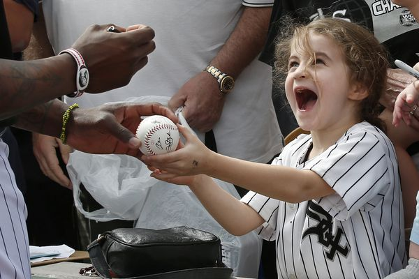 Six-year-old Joan Stiltner, of Chicago, helps hold a ball for Chicago White Sox left fielder Joel Booker to autograph before the team's spring training baseball game against the Milwaukee Brewers on Thursday, March 7, 2019, in Glendale, Ariz. (AP Photo/Sue Ogrocki)