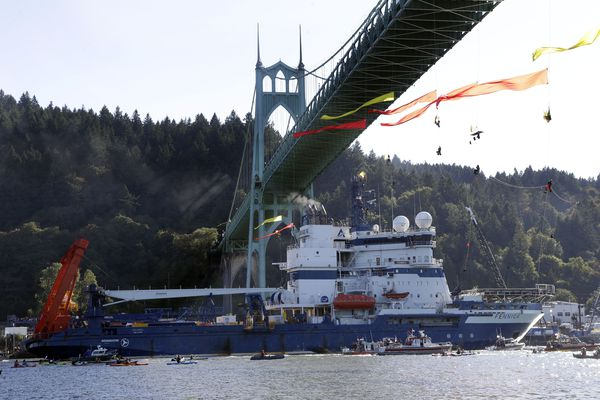 The Royal Dutch Shell-contracted icebreaker Fennica heads up the Willamette River on its way to Alaska beneath protesters still hanging from the St. Johns Bridge in Portland, Ore., on Thursday.