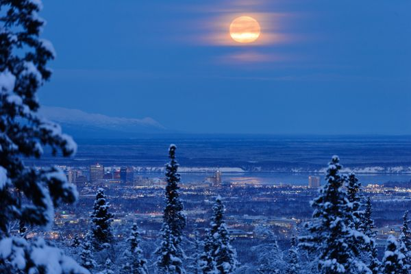 The full moon sets in this view over Anchorage from near the Prospect Heights Trailhead of Chugach State Park on December 22, 2018. (Marc Lester / ADN)