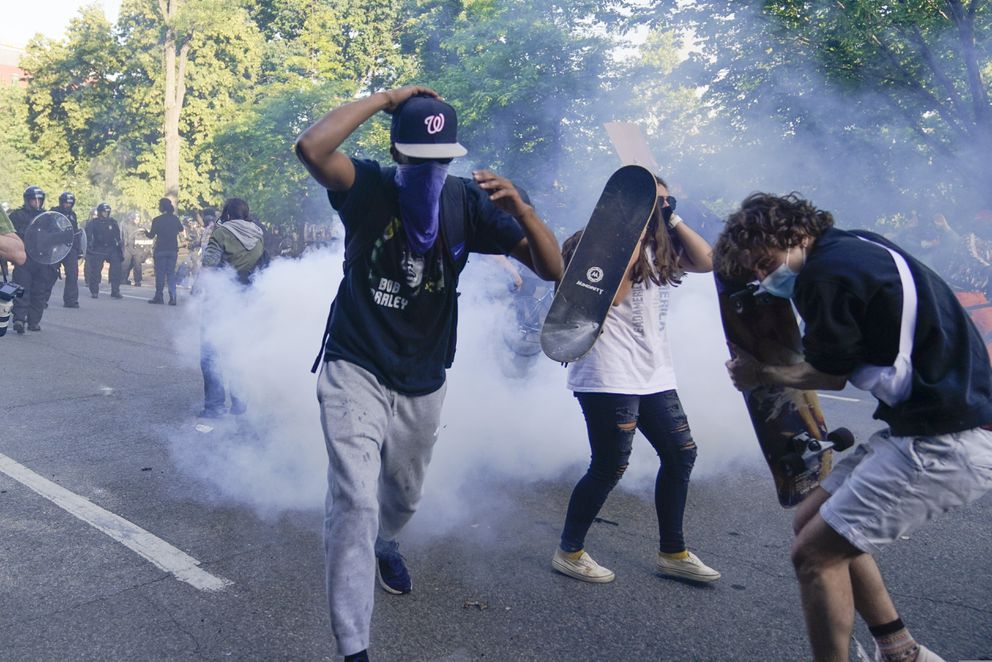 Demonstrators, who had gathered to protest the death of George Floyd, begin to run from tear gas used by police to clear the street near the White House in Washington, Monday, June 1, 2020. Floyd died after being restrained by Minneapolis police officers. (AP Photo/Evan Vucci)