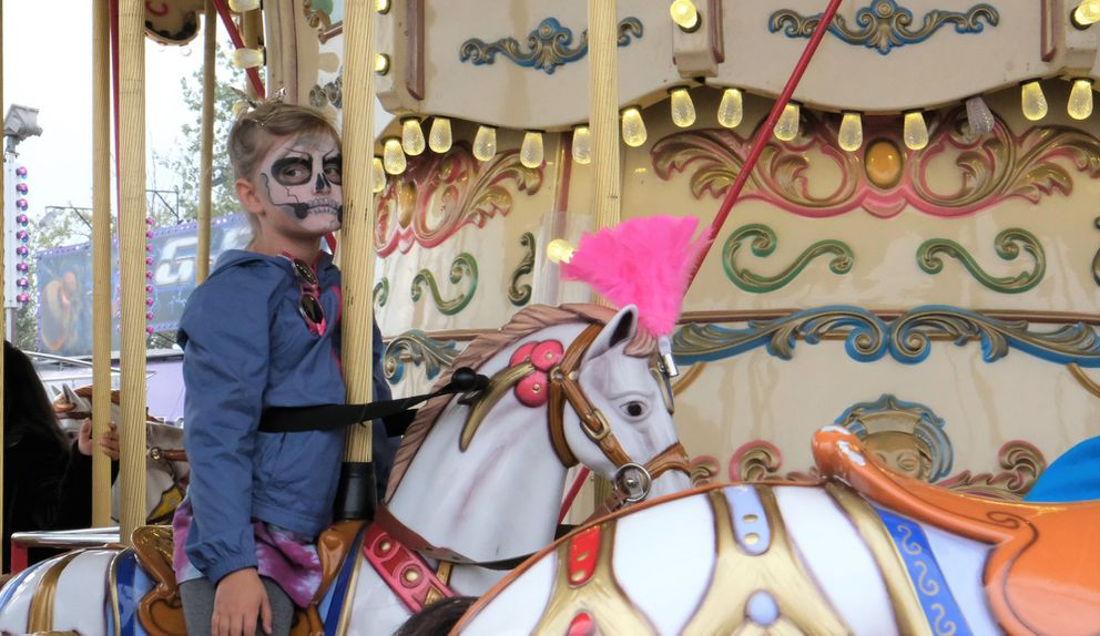 Grace Bacher, 7, tries not to have too much fun while on the carousel at the Alaska State Fair Sunday, Aug. 25, 2019 (Photo by Samantha Davenport)