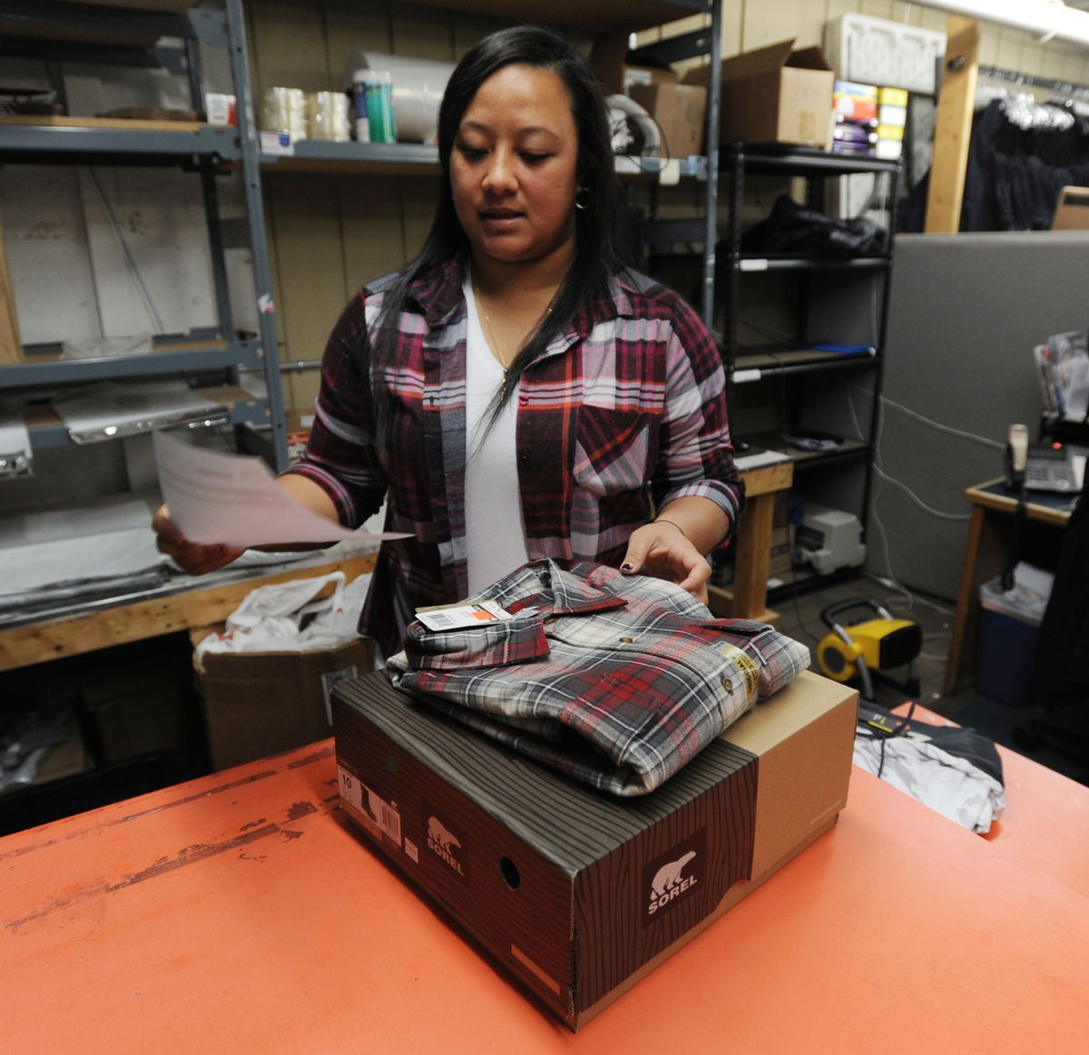Erlene Iese, a mail order associate at Big Ray's on Fourth Avenue in Anchorage, prepares a COD order that will be shipped to the village of Galena on the Yukon River. (Bill Roth / ADN)