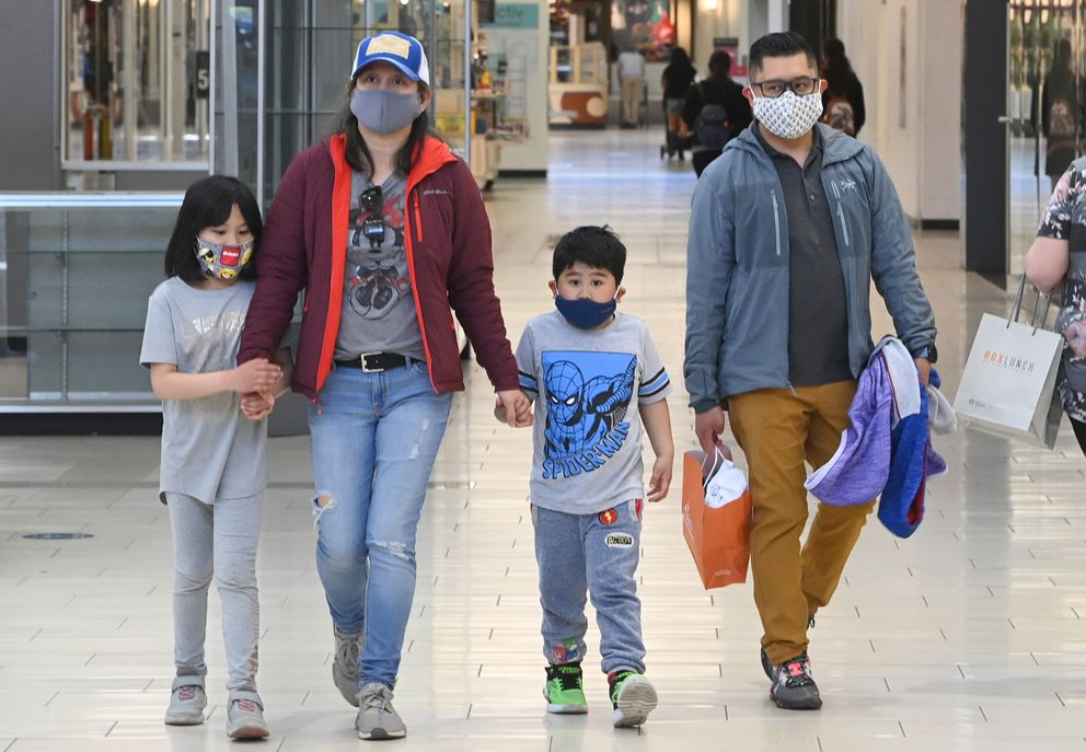 Glen Lavarias walks with his wife Mathilda and their children Kassandra, 7, and Laurence, 4, wore masks while shopping in the Dimond Center on Monday, May 17, 2021. Because of their work they 'wore masks to help protect their children and extended family, ' said Lavarias. 'Rather safe than sorry. ' (Bill Roth / ADN)