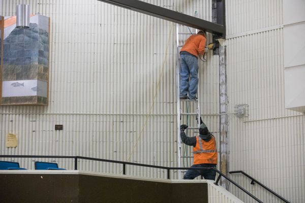 Workers remove damaged non-structural concrete siding inside Gruening Middle School in Eagle River on Tuesday, Dec. 4, 2018. Parts of the school have not been inspected after Friday's 7.0 earthquake, and officials are waiting for the results of those inspections before making a determination about whether to open the school next week. (Loren Holmes / ADN)
