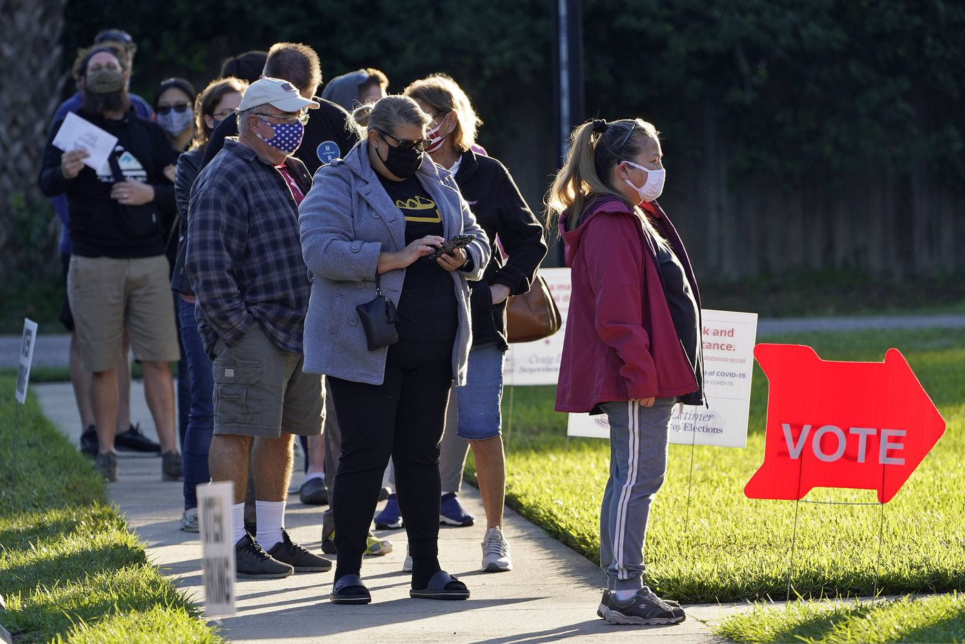 People wear protective face masks as they wait in line to vote at the Bell Shoals Baptist Church on election day Tuesday, Nov. 3, 2020, in Brandon, Fla. (AP Photo/Chris O'Meara)