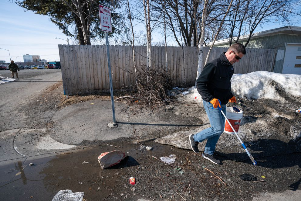 Downtown business owner Rob Cupples picks up trash next to his property at 3rd Avenue and Hyder Street on Thursday, April 9, 2020. Cupples operates short-term rentals through Airbnb. (Loren Holmes / ADN)