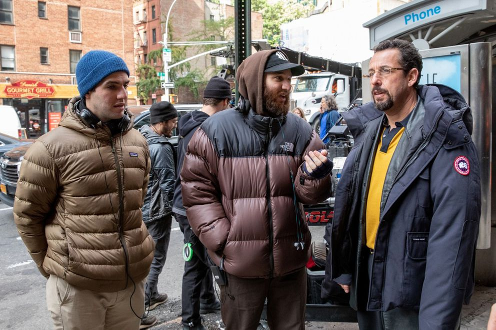 From left, writer-directors Benny and Josh Safdie chat with Adam Sandler on the set of 'Uncut Gems. ' (Julieta Cervantes/A24)