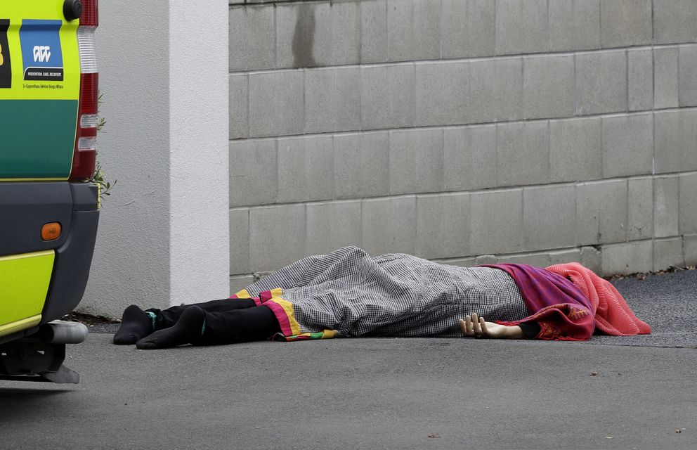 A body lies on the footpath outside a mosque in central Christchurch, New Zealand, Friday, March 15, 2019, after a mass shooting. (AP Photo/Mark Baker)