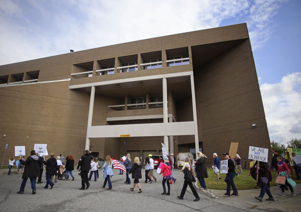 Protestors walk around the Loussac Library looking for an entrance into the building where the Anchorage Assembly gathered for a meeting on Aug. 11, 2020. (Emily Mesner / ADN)