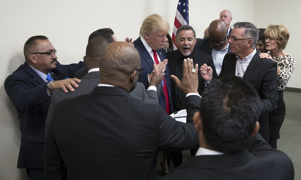 Donald Trump bows his head as Pastor Paul Marc Goulet, center, leads a prayer at the International Church of Las Vegas, Oct. 5, 2016. Trump met with church pastors and vowed that if elected he would strike down the Johnson Amendment, which restricts churches and other non-profit organizations from endorsing political candidates. (Stephen Crowley / The New York Times)