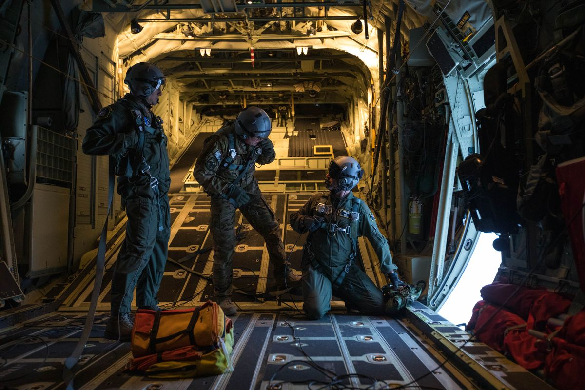 From left, Master Sgt. Ryan Conti, Staff Sgt. Matt Duncan, and Tech. Sgt. Eric Dickerson, loadmasters with the 211th Rescue Squadron, practice dropping small aid packages from the open door of an Alaska Air National Guard HC-130J Combat King II on Wednesday, Jan. 9, 2019 at Joint Base Elmendorf-Richardson. The airplane is one part of the