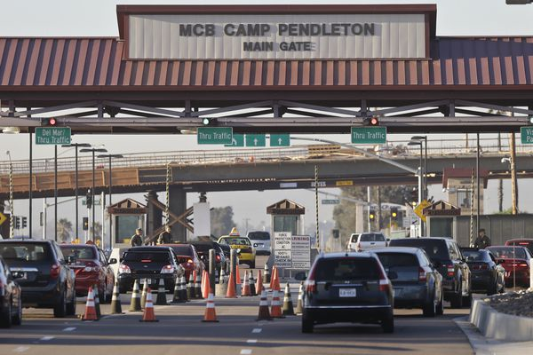 FILE - In this Nov. 13, 2013 file photo vehicles file through the main gate of Camp Pendleton Marine Base at Camp Pendleton, Calif. A human smuggling investigation by the military led to the arrest of 16 Marines Thursday, July 25, 2019 while carrying out a battalion formation at California's Camp Pendleton, a base about an hour's drive from the U.S.-Mexico border. (AP Photo/Lenny Ignelzi, File)