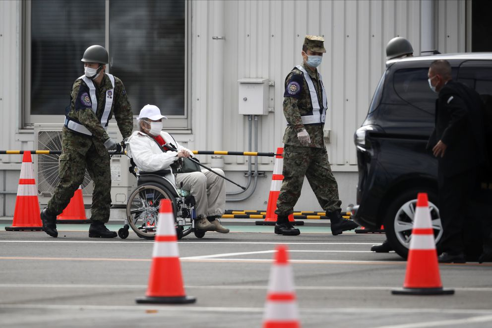 An unidentified passenger on a wheelchair is escorted after he disembarked from the quarantined Diamond Princess cruise ship Wednesday, Feb. 19, 2020, in Yokohama, near Tokyo. Passengers tested negative for COVID-19 started disembarking Wednesday. (AP Photo/Jae C. Hong)