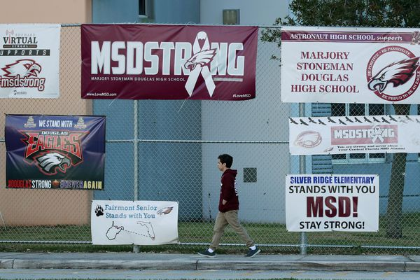 A student walks past signs outside Marjory Stoneman Douglas High School during the one-year anniversary of the school shooting, Thursday, Feb. 14, 2019, in Parkland, Fla. A year ago on Thursday, 14 students and three staff members were killed when a gunman opened fire at the high school. (AP Photo/Wilfredo Lee)