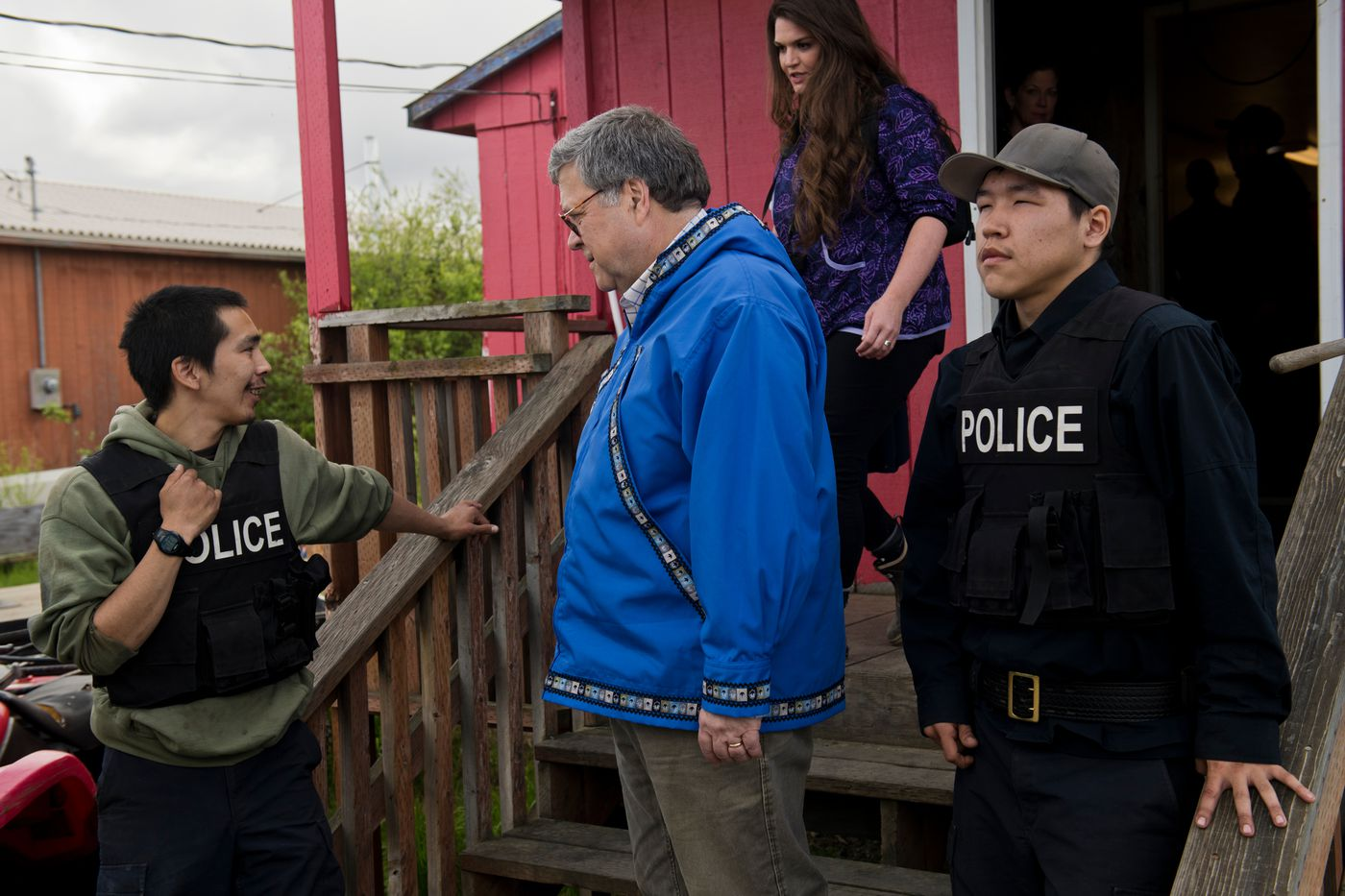 U.S. Attorney General William Barr talks with village police officer Phillip Wilson, left, and tribal police officer Joseph Steven Jr. outside the Napaskiak public safety building. (Marc Lester / ADN)