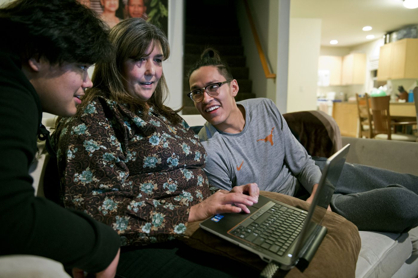 Taqulik Hepa browses through family photos on a computer with her sons Keoni, left, and Kamaka. Taqulik divides her time between home in Utqiagvik and being with her husband and sons in Portland. (Marc Lester / ADN)