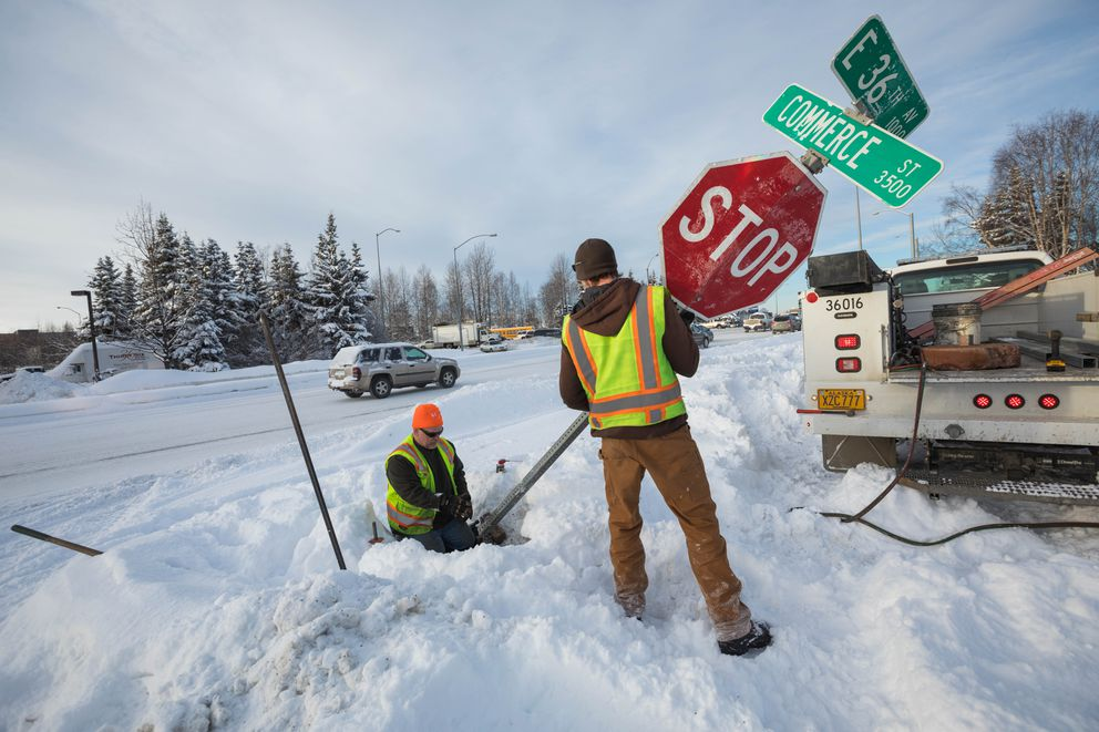Municipality of Anchorage employees Bob Ward, left, and Derek Peters fix a stop sign that was knocked over in Midtown. (Loren Holmes / ADN)