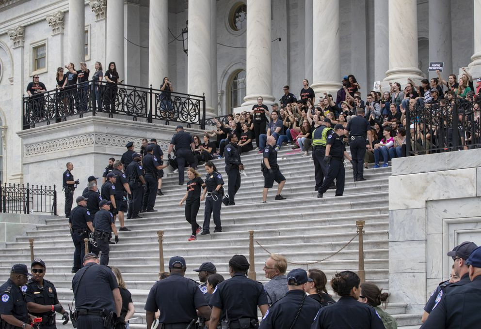 Crowds of activists are arrested after they rushed past barriers and protested from the steps of the Capitol before the confirmation vote on President Donald Trump's Supreme Court nominee, Brett Kavanaugh, in Washington, Saturday, Oct. 6, 2018. (AP Photo/J. Scott Applewhite)