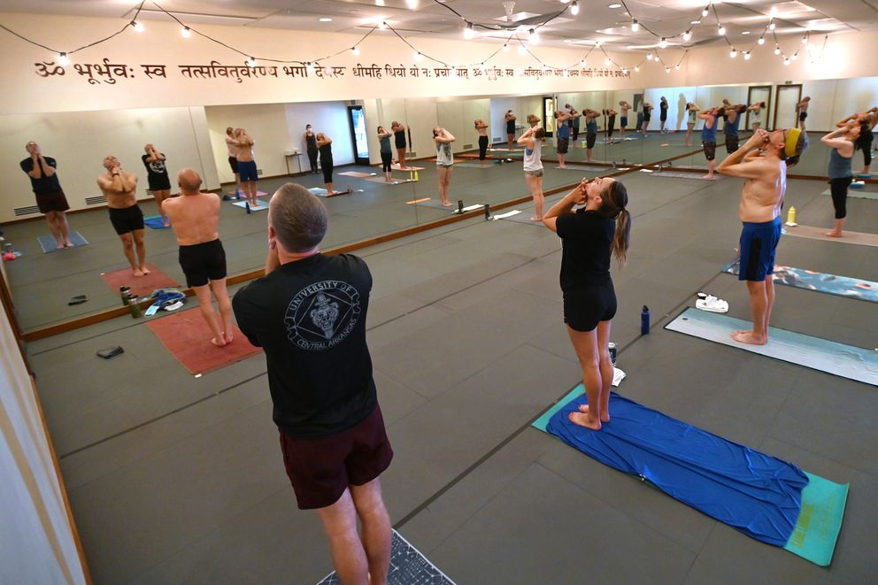 Anchorage Yoga & Cycle instructor Sara Forbes-Hall, white shirt near the mirror, leads a Hot 75 with Music yoga class on Tuesday, July 7, 2020. (Bill Roth / ADN)