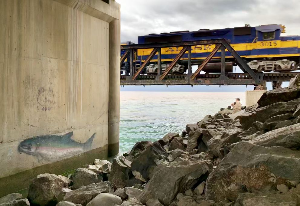 An angler fishes for salmon at the mouth of Bird Creek as an Alaska Railroad train passes on Wednesday, Aug. 14, 2019. (Matt Tunseth / ADN)