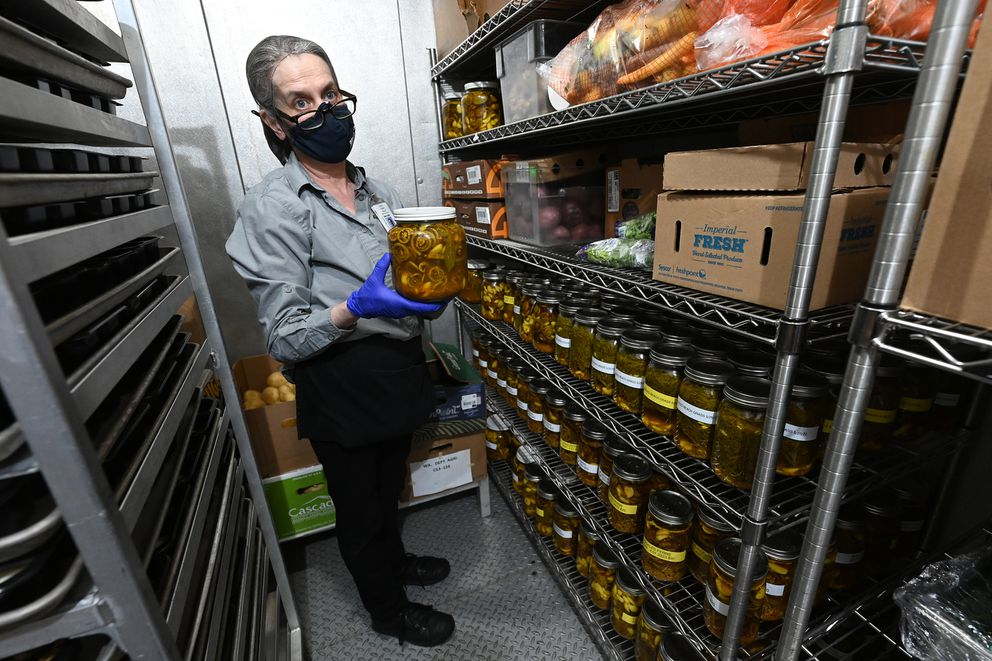 Virginia Mocan, retail supervisor at the Alaska Native Medical Center cafeteria, holds a jar of pickled fiddlehead ferns on Sunday, May 23, 2021. (Bill Roth / ADN