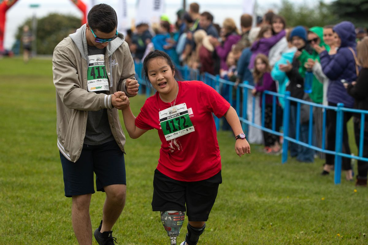 Leighanna Kolp, who was born without a leg and has cerebral palsy, makes her way to the finish line of the5K race with the help of brother Tanner. (Loren Holmes / ADN)